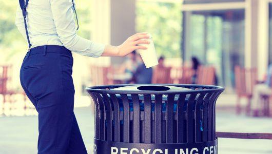 Woman putting litter in a black recycling bin