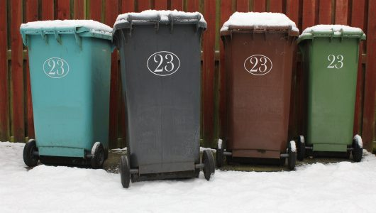 four household and commercial waste bins