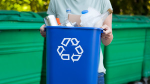 Woman carrying a blue business recycling bin
