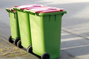 Three green wheelie bins outside