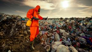 Person in orange hazmat suit on landfill