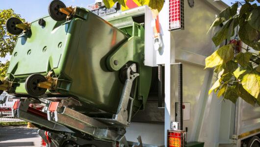 Truck lifting waste bin in summer sunshine